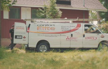 Vue de côté d'un camion blanc lettré Confort Élite sur pelouse
