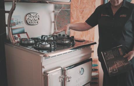 Homme se tenant à côté d'une cuisinière au gaz vintage
