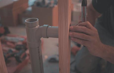 Homme installant un tuyau dans une maison en construction