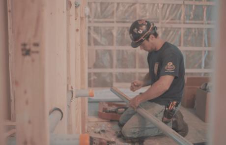 Homme mesurant un tuyau dans une maison en construction