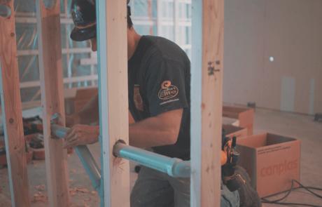 Homme installant un tuyau dans les murs de division